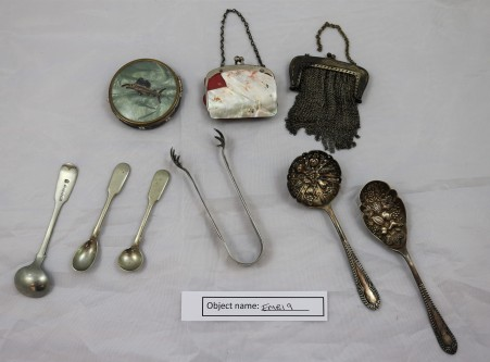 EMB19: collection of objects from the owner's mother, including a sail fish compact, mother of pearl bag, jam spoons, sugar tongs, coin purse and condiment spoons
