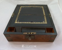 EMB20: travel writing desk, handed down from the owner's grandfather in 1958 (when he was 9). It used to have a plaque on it to his grandfather from his family, as it was presented to him on his 21st Birthday. The desk is made of walnut with gold embossed leather, and has a secret compartment