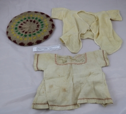 CRO3: The dress at the bottom of the image was handmade for a doll that belonged to the owner's husbands grandma. The baby's top and beret belonged to her father-on-law, and are 100 years old.