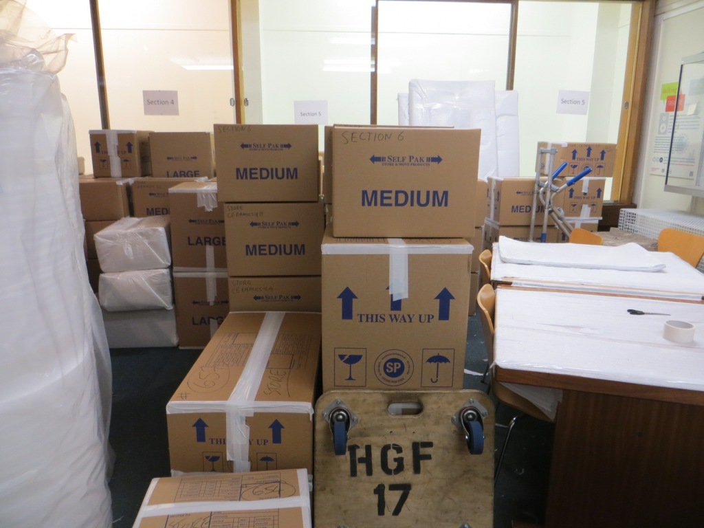 A stack of boxes and packing materials in the old Craven Museum, with a desk to the right of the boxes and empty museum cases behind.
