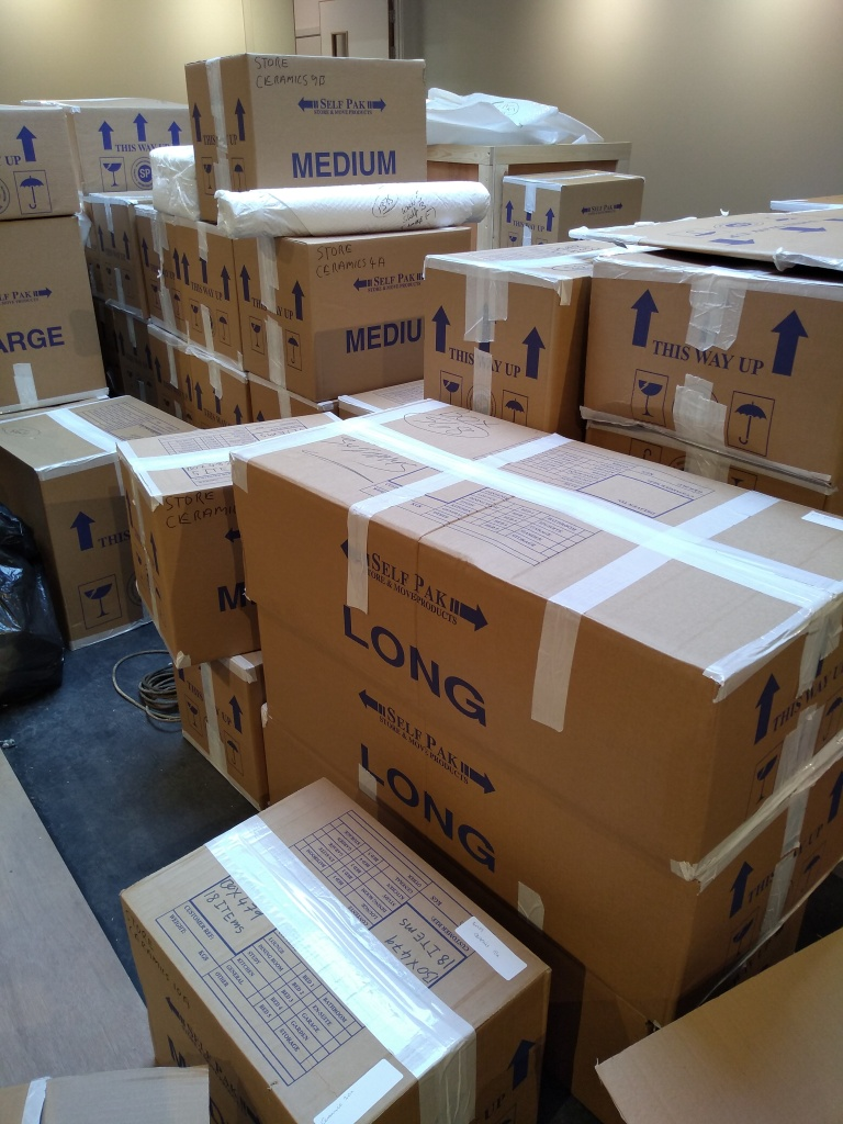 Multiple stacks of cardboard boxes of different shapes and sizes.