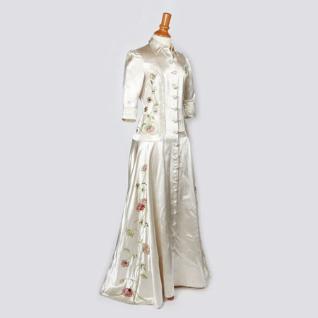 Creamy white silk wedding dress displayed on a dress stand with pink flowers and green stems visible down the left hand side. The dress is floor length with three quarter length sleeves and a pointed collar. Buttons run down the front.