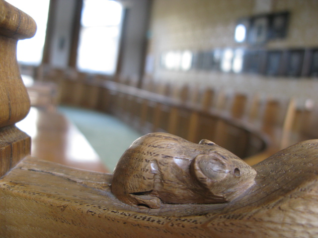 A wooden carved mouse on the top of a piece of furniture in the Council Chamber at Skipton Town Hall.