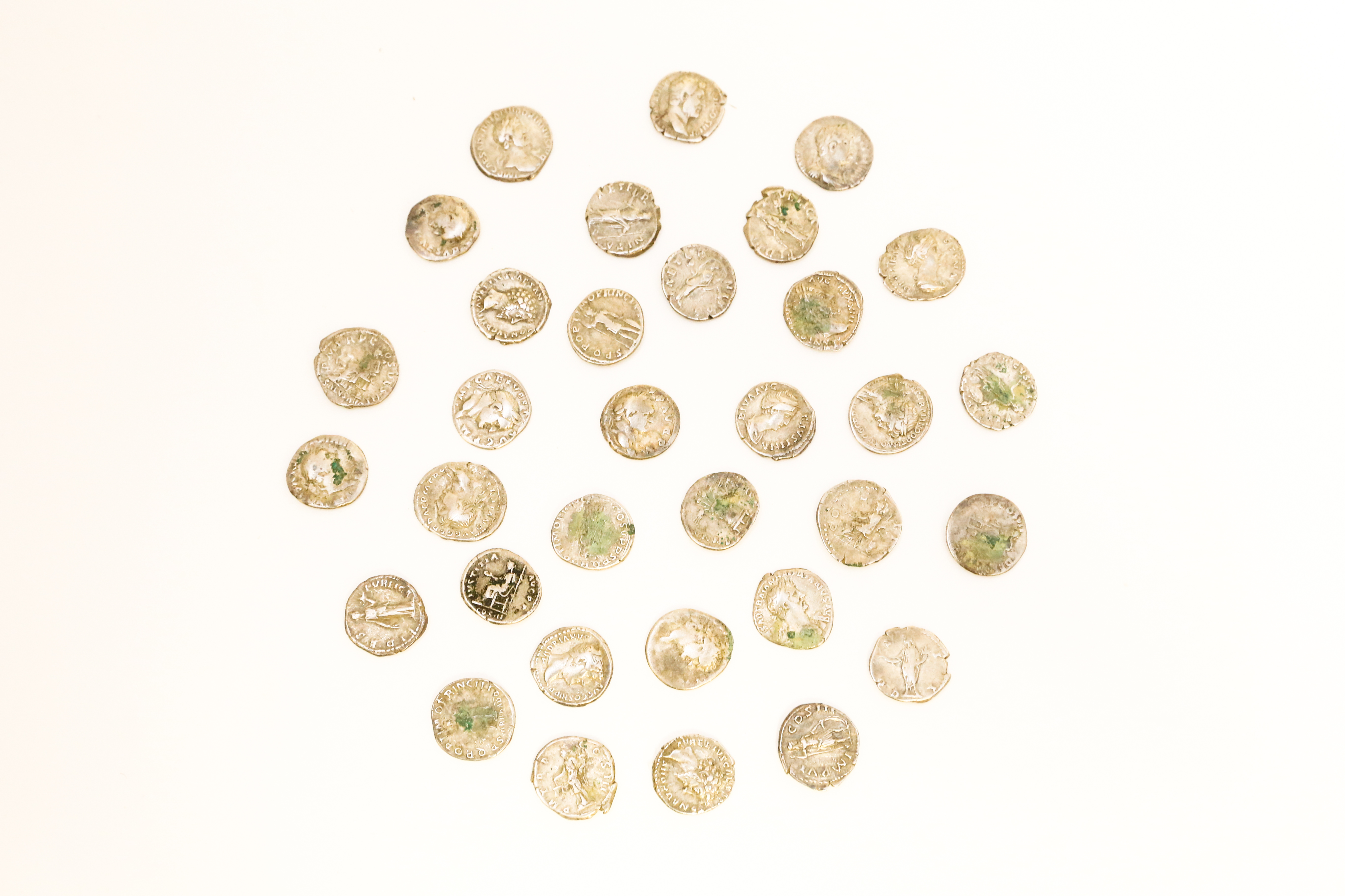 33 small metal coins. Roman emperor heads can be seen stamped on some of the coins. Some are tarnished.